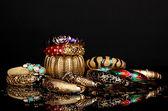 Piękne złote bransoletki na białym tle na czarnym tle — Zdjęcie stockowe