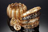 Vackra gyllene armband och ringar på grå bakgrund — Stockfoto
