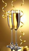 Glasses of champagne and streamer on yellow background — Stock Photo