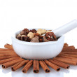 Composition of mortar with nuts and cinnamon isolated on white - Stock Photo