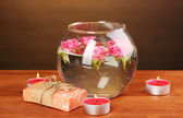 Spa composition of candles, soap and pink roses floating on wooden background — Stock Photo