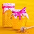 Jars of honey and wooden drizzler on yellow honeycomb background — Stock Photo #10125675