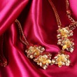Beautiful gold necklace on red silk fabric - Stock Photo