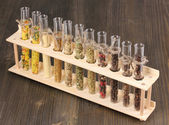 Various spices in tubes on wooden background — Stock Photo