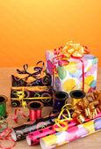 Gigts, carta, nastri e fiocchi sul tavolo di legno su sfondo giallo — Foto Stock