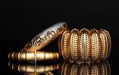 Pulseras de oro hermosas aisladas sobre fondo negro — Foto de Stock