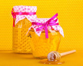 Jars of honey and wooden drizzler on yellow honeycomb background — Stock Photo