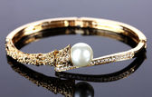 Beautiful golden bracelet with pearl on grey background — Stock Photo