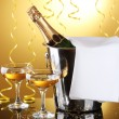 Champagne bottle in bucket with ice and glasses of champagne, on yellow background - Foto Stock
