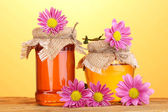 Sweet honey in jars on wooden table on yellow background — Stock Photo