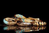 Beautiful golden bracelets isolated on black background — Stock Photo