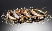 Beautiful golden bracelets on grey background — Stock Photo