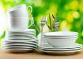 Clean dishes on wooden table on green background — Stok fotoğraf