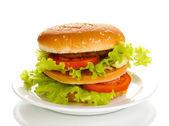 Big and tasty hamburger on plate isolated on white — Stock Photo
