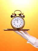 Hand in glove holding silver tray with alarm clock on yellow background — Stock Photo