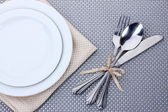 White empty plates with fork, spoon and knife tied with a ribbon on a grey tablecloth — Stock Photo