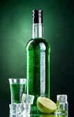 Fles en glas van absint met limoen en ijs op groene achtergrond — Stockfoto