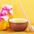 Stock Photo: Jars of honey, bowl and wooden drizzler with honey on yellow honeycomb background