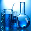 Test-tubes with blue liquid on blue background - Stock Photo