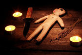 Chłopiec lalki voodoo na drewnianym stole w blasku świec — Zdjęcie stockowe