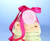 Colorful towels with ribbon on blue background — Stock Photo