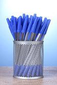 Blauwe pennen in metalen cup op houten tafel op blauwe achtergrond — Stockfoto