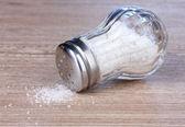 солонка стекла с солью на деревянных фоне — Стоковое фото