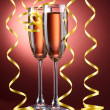 Glasses of champagne and streamer on red background — Stock Photo
