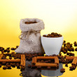 Composition of canvas sack and the cup with coffee beans on bright background. Hot. — Stock Photo #10155001