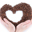Hand holding heart of coffee beans on white background — Stock Photo