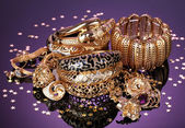 Beautiful golden jewelry on purple background — Stockfoto