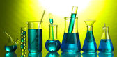 Test-tubes with blue liquid on green background — Stock Photo