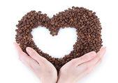 Kahve çekirdekleri kalbinde beyaz arka plan üzerinde tutan el — Stok fotoğraf