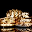 Beautiful golden bracelets isolated on black background — Stock fotografie