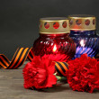 Memory lantern with candles, red carnations and St. George ribbon on wooden table on grey background — Stock Photo #10197768