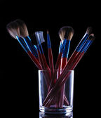 Make-up brushes in glass cup on grey background — Stock Photo