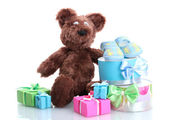 Beautiful gifts, baby's bootees and bear toy isolated on white — Stock Photo