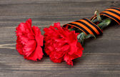 Carnations and St. George's ribbon on grey wooden background — Stock Photo