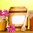 Sweet honey in jars and barrel with drizzler on wooden table on green background - Stock Photo