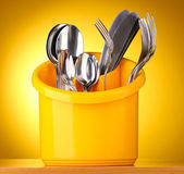 Kitchen cutlery, knives, forks and spoons in yellow stand on yellow background — Stock Photo