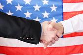 Business handshake on american flag background — Stock Photo