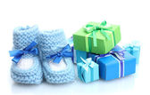 Beautiful gifts and baby's bootees isolated on white — Stock Photo