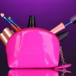 Make up bag with cosmetics and brushes on violet background — Stock Photo #10226473