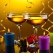 Glasses of champagne, candles, gifts and streamer on yellow background - Stock Photo
