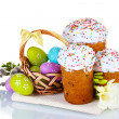 Beautiful Easter cakes, colorful eggs in basket and flowers isolated on white — Stock Photo #10229240