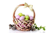 Basket with Easter eggs and pussy-willow twigs isolated on white — Stock Photo