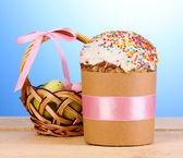 青色の背景に木製のテーブルの上のバスケットに卵と美しいイースター ケーキ — ストック写真