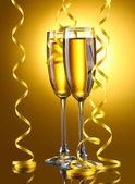 Glas champagne och streamer på gul bakgrund — Stockfoto