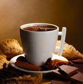 Taza de chocolate caliente, palitos de canela, nueces y chocolate en tabla de madera sobre fondo marrón — Foto de Stock