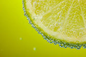 Slice of lemon in the water with bubbles — Stock Photo
